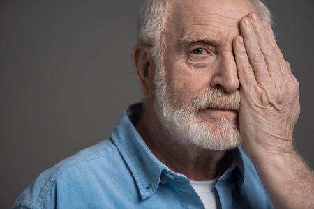senior bearded man reviewing sight geïsoleerd op grijs in studio Stockfoto
