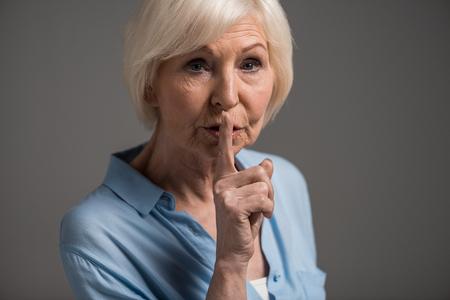 Portret van senior vrouw met hush gebaar