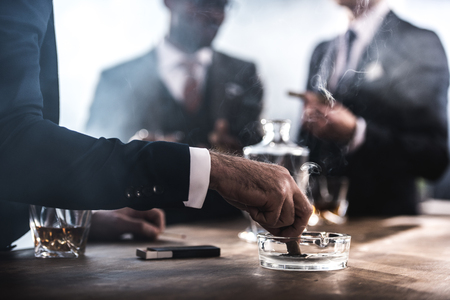 partial: businessman extinguishing cigar in glass ashtray Stock Photo