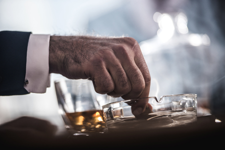 businessman extinguishing cigar in glass ashtray Фото со стока