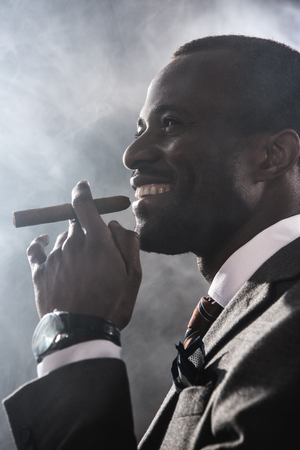 smiling confident man smoking cigar indoors