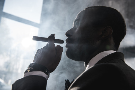 confident african american man smoking cigar indoors
