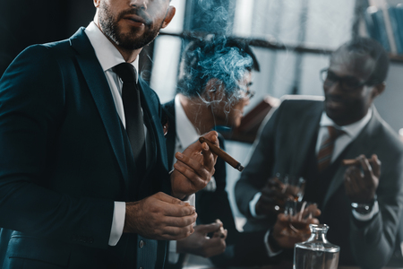 businessman smoking cigar with multicultural business team