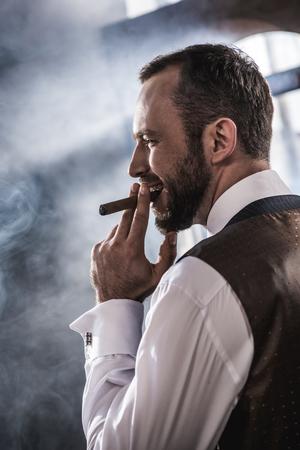 Lächelnd zuversichtlich, Mann raucht Zigarre im Haus Standard-Bild - 80600084
