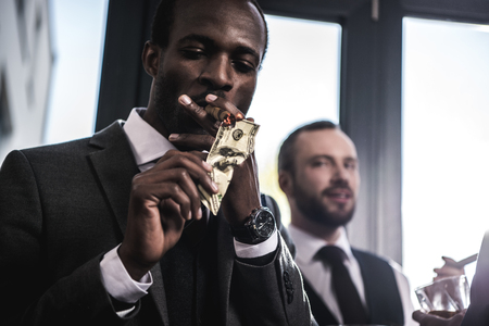 businessman lighting cigar with dollar banknote indoors Фото со стока