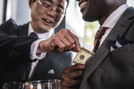 partial: two smiling businessmen talking and holding dollar banknote