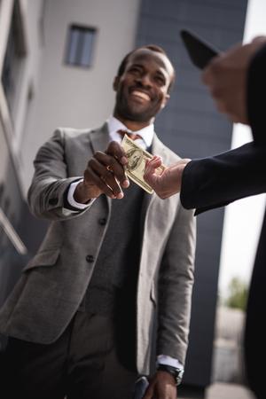 african american businessman in formalwear taking money outdoors Reklamní fotografie
