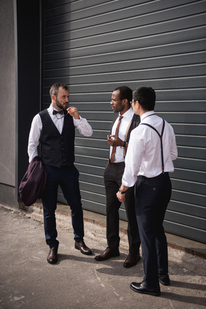 boomers: young multiethnic businessmen in formalwear talking at break outdoors Stock Photo