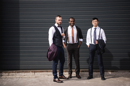 boomers: young stylish multiethnic businessmen in formalwear standing outdoors