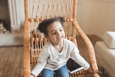 Kleines Afroamerikanermädchen mit digitaler Tablette und auf Schaukelstuhl zu Hause sitzen Standard-Bild - 80599601