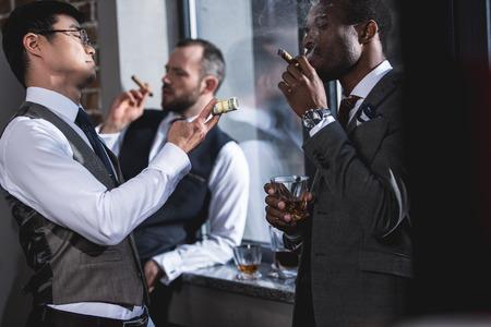 to spend: businessmen smoking cigars together during break