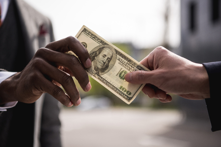 anonymous businessmen hands holding one hundred dollars banknote
