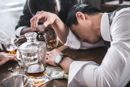 drunk colleagues sleeping at table while spending time together