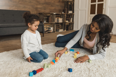 mother and little daughter playing with cubes together