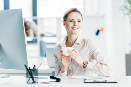 looking aside: smiling businesswoman drinking coffee while sitting at office