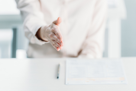 businesswoman extending hand for handshake with document on tabletop Stock Photo