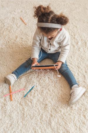 little girl in headphones sitting on floor and using digital tablet