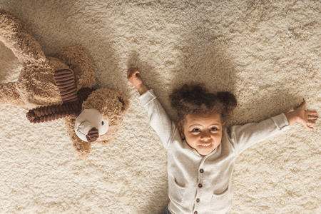 adorable little african american girl lying on carpet at home