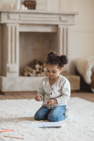 little african american girl drawing with pencils and sitting on carpet at home