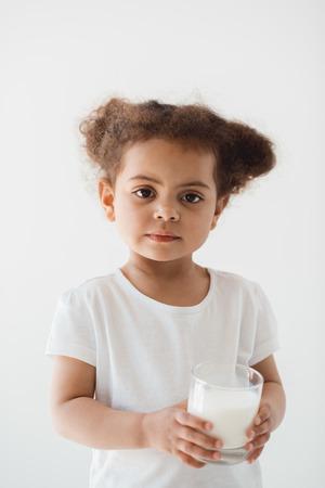 작은 아이 소녀 흰색에 고립 된 우유의 유리를 잡고