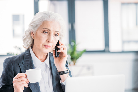 senior businesswoman holding coffee cup and talking on smartphone