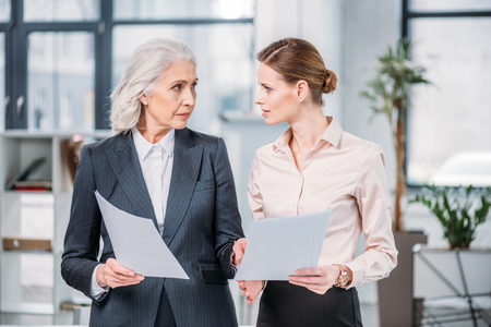 businesswomen standing and holding documents and looking at each other