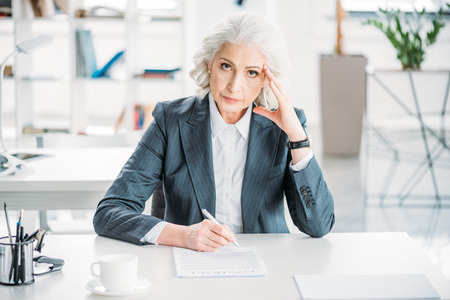 businesswoman sitting at workplace and signing contract