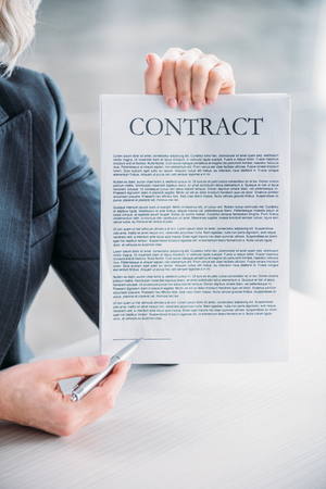partial: businesswoman sitting at workplace and pointing at contract
