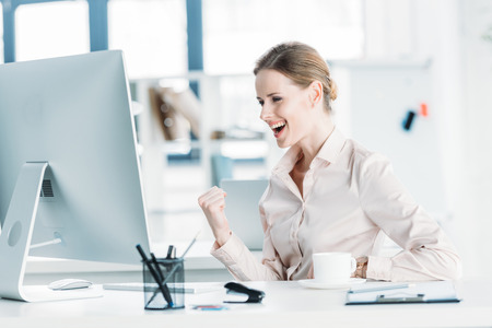 happy businesswoman sitting near modern computer at office