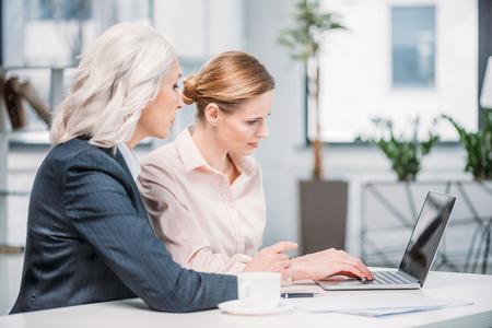 Femmes d & # 39 ; affaires avec ordinateur portable discuter projet d & # 39 ; affaires sur la Banque d'images - 80599772
