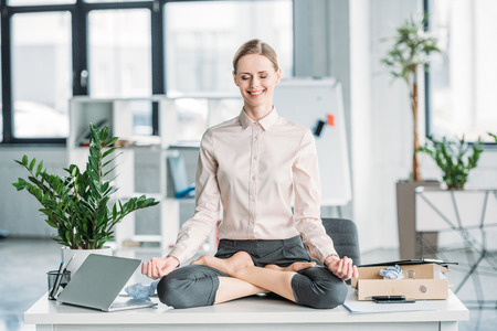 businesswoman meditating in lotus position on messy table in office