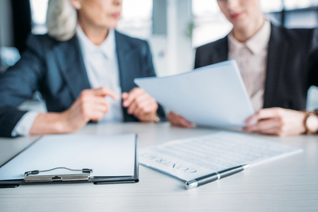 two businesswomen discussing business project on meeting in office, clipboard and contract on foreground