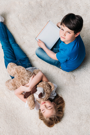 girl with teddy bear and boy with digital tablet on carpet at home Stok Fotoğraf