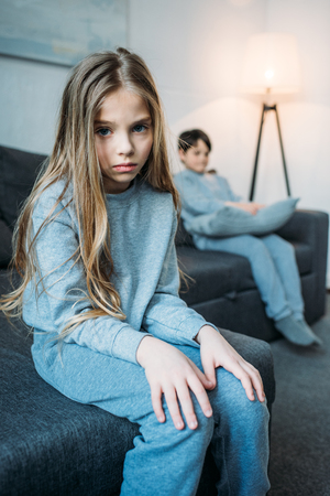 little girl in pajamas looking at camera while little brother sitting behind Stok Fotoğraf