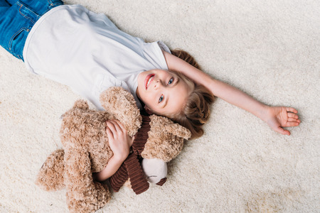 girl holding teddy bear and looking at camera while lying on carpet at home