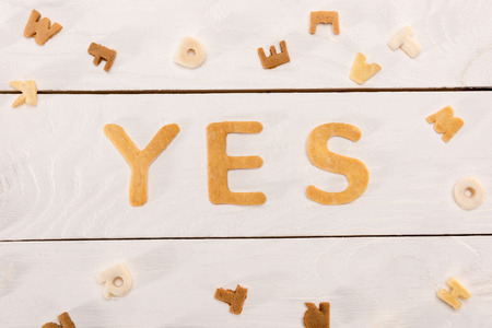 word yes from breakfast cereal letters and alphabet corn flakes on wooden table Фото со стока