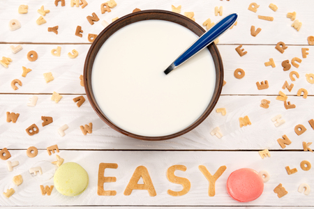 Close-up view of milk and spoon in bowl, word easy from breakfast cereal letters