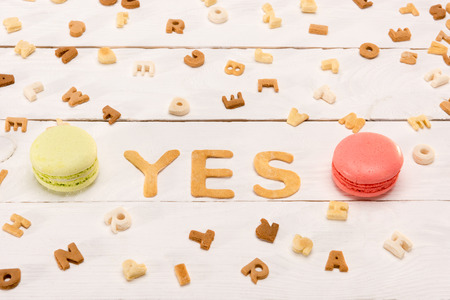 word yes from breakfast cereal letters and alphabet corn flakes with macarons on wooden table