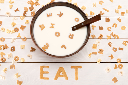 milk and spoon in bowl, word eat from breakfast cereal letters and alphabet corn flakes on wooden table