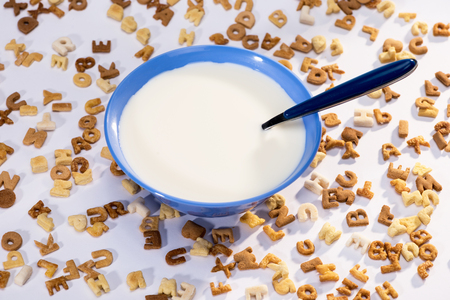 Close-up view of breakfast cereal alphabet, milk in bowl and spoon