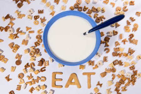 Top view of breakfast cereal alphabet, milk in bowl and word eat