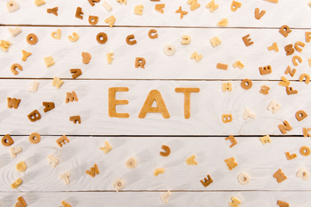 word eat from breakfast cereal letters and alphabet corn flakes on wooden table