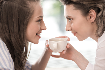 boomers: smiling girlfriends drinking coffee and looking at each other