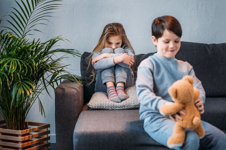 sly boy holding teddy bear while offended girl sitting on sofa
