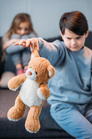 preadolescent: boy holding teddy bear while offended girl sitting on sofa Stock Photo