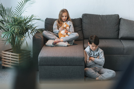 girl with teddy bear on sofa and boy sitting with arms crossed Stock fotó