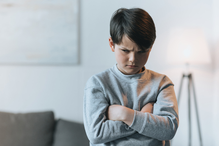upset little kid boy with arms crossed