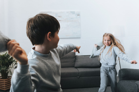 boy and girl playing pillow fight at home