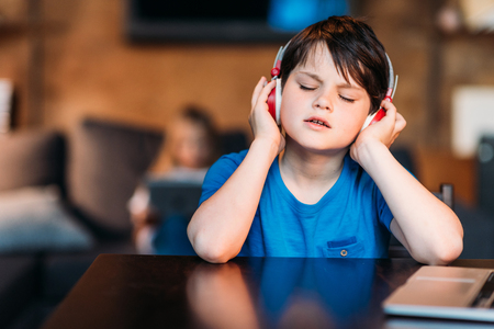 preadolescent: concentrated little boy listening music in headphones Stock Photo