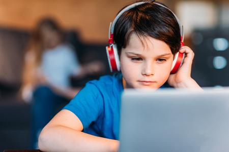 preadolescent: focused little boy in headphones using laptop Stock Photo
